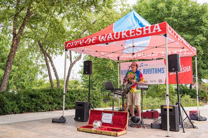 A musician performing at riverside rhythms.
